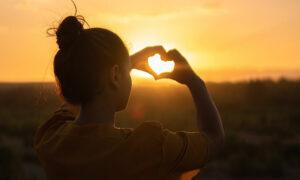 Das Bild zeigt ein Mädchen in der Sonne, welches ihre Hände zu einem Herz formt. Es steht als Metapher für die Social Media Kanäle der Praxis für Familiengesundheit. MVZ für Innere Medizin, Endokrinologie, Diabetologie und Kinder- und Jugendpsychiatrie und -psychotherapie - KJP