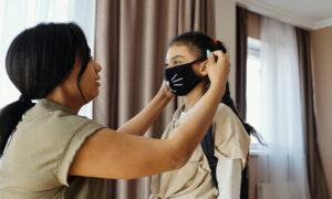 Das Bild zeigt eine Mutter, welches ihrem Kind eine Maske anzieht. Es steht als Metapher für die Corona Hygiene Regeln in der Praxis für Familiengesundheit in Essen. MVZ für Innere Medizin, Endokrinologie, Diabetologie und Kinder- und Jugendpsychiatrie und -psychotherapie - KJP & Hausärzte