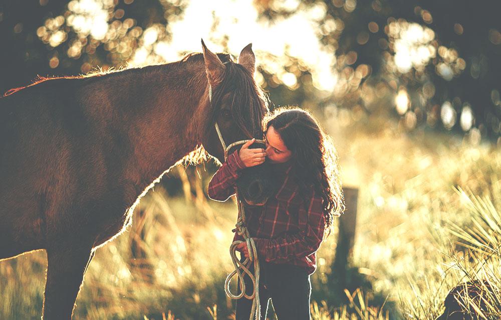 Das Bild zeigt eine Frau mit Pferd. Es steht als Metapher für die Philosophie und die ganzheitliche Medizin der Praxis für Familiengesundheit in Essen. MVZ für Innere Medizin, Endokrinologie, Diabetologie und Kinder- und Jugendpsychiatrie und -psychotherapie - KJP & Hausärzte