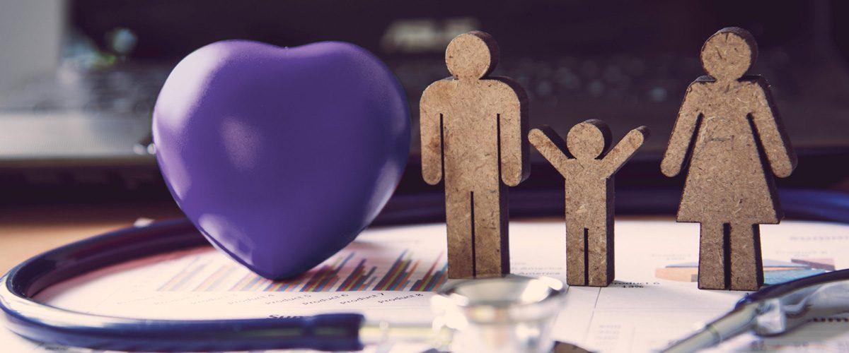 Das Bild zeigt kleine Figuren aus Holz, welche eine Familie darstellen, neben einem lila Herz. Es ist eine Metapher für das Angebot der Allgemeinmedizin / Hausärztlichen Betreuung in der Praxis für Familiengesundheit in Essen. MVZ für Innere Medizin, Endokrinologie, Diabetologie und Kinder- und Jugendpsychiatrie und -psychotherapie - KJP & Hausärzte Essen