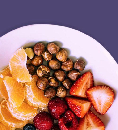 Das Bild zeigt einen Teller voller Obst und Nüssen und gesundem Essen. Es steht für das Angebot der Prävention / der Präventionsmedizin in der Praxis für Familiengesundheit in Essen. MVZ für Innere Medizin, Endokrinologie, Diabetologie und Kinder- und Jugendpsychiatrie und -psychotherapie - KJP & Hausärzte Essen
